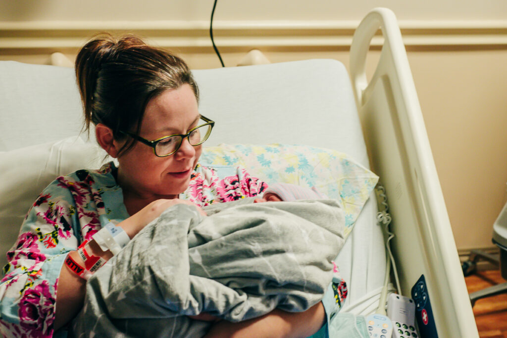 mother holding baby after birth - Trout River Photography
