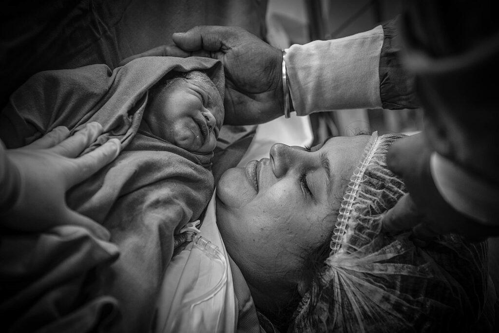 newborn baby being presented to mom - Delhi Birth Photographer - Shipra & Amit Chhabra