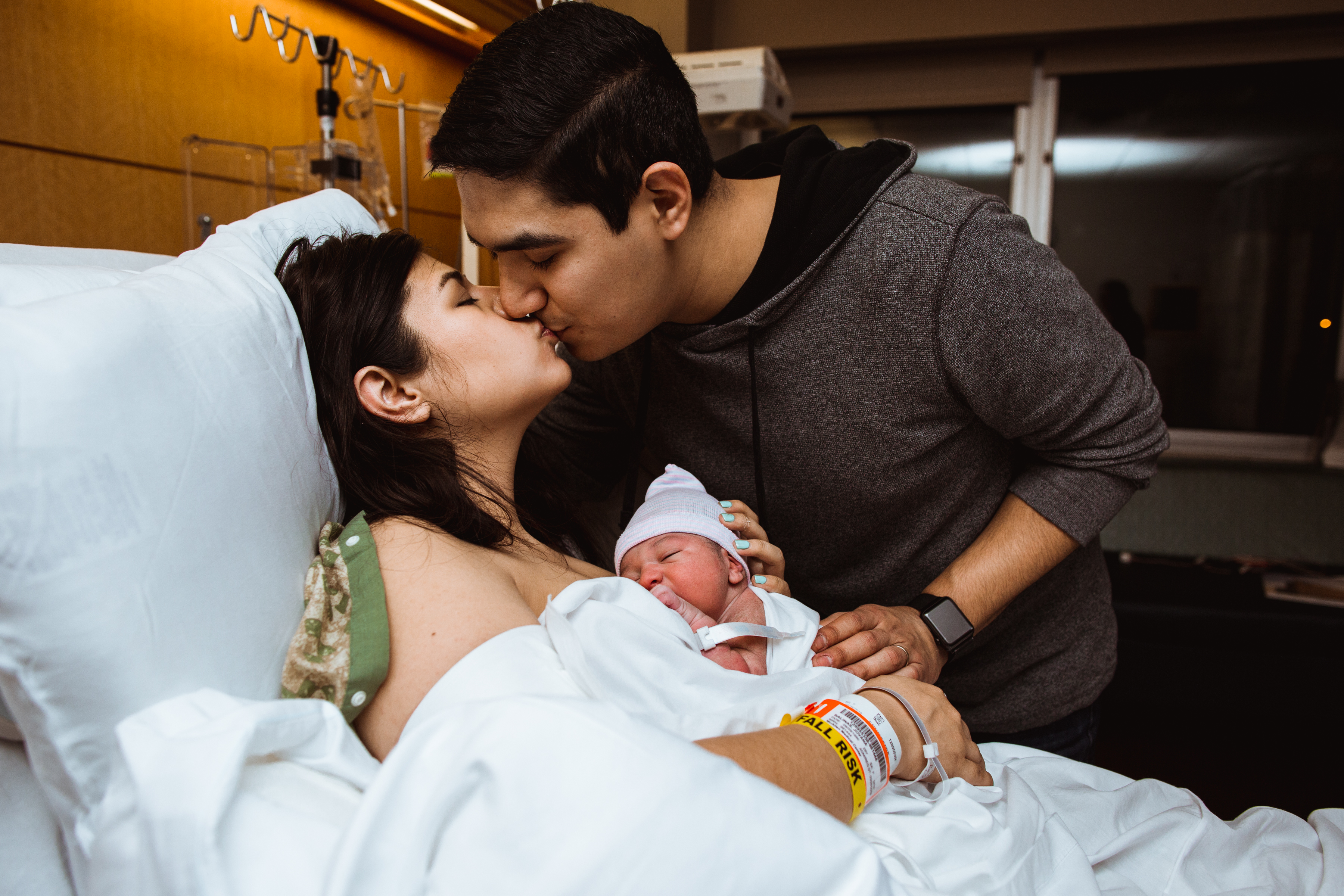 New-father-kisses-his-partner-on-the-lips-as-she-holds-their-new-born-baby-boy-on-her-chest