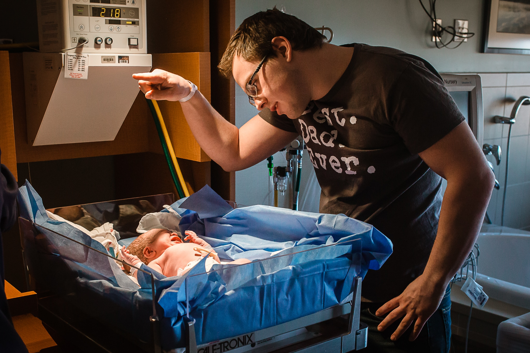 dad of newborn baby is blocking the light from the warmer so it does not shine in baby's eyes