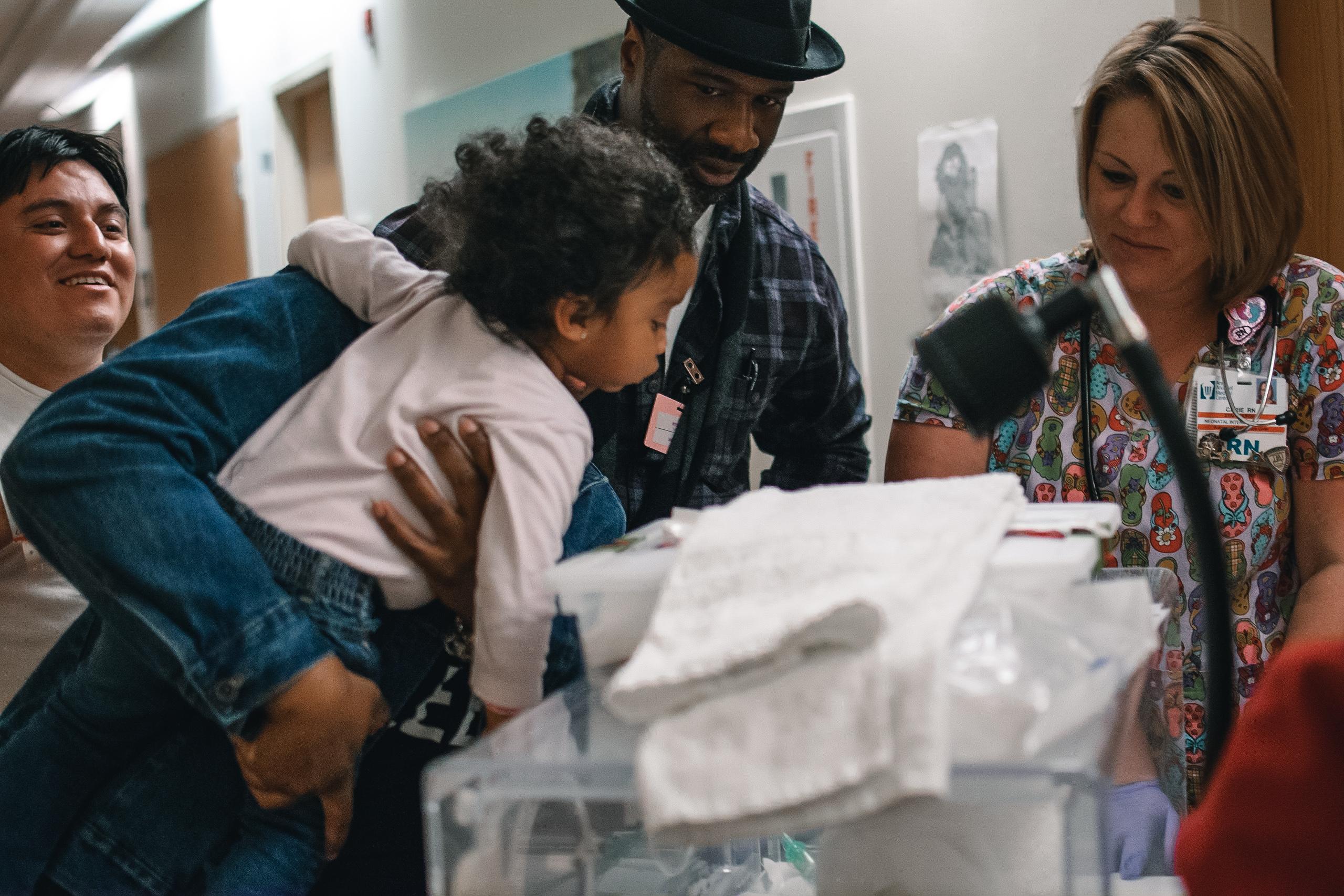 family surrounding newborn baby in NICU incubator