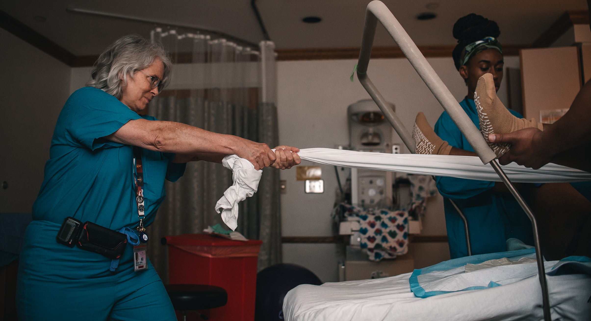 obgyn tugging on a sheet with a laboring woman